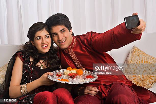 brother and sister taking a picture of themselves with a mobile phone at raksha bandhan - raksha bandhan stock photos and pictures