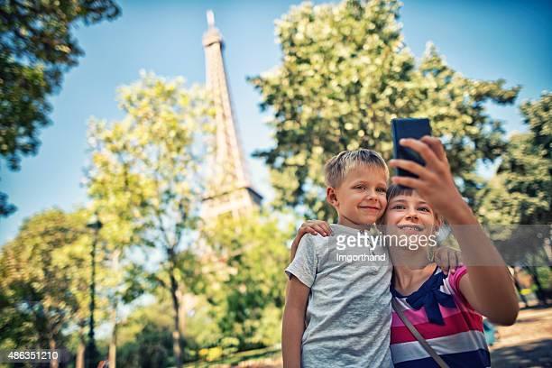 Frère et sœur prenant selfie à proximité de la tour Eiffel