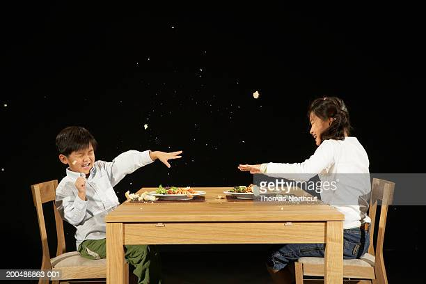Brother and sister (4-10) throwing food at one another at table