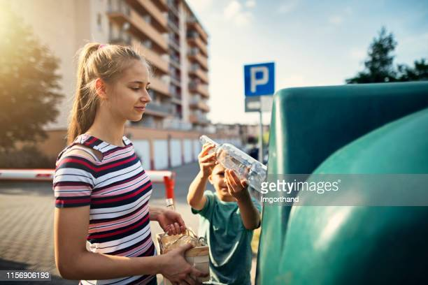 brother and sister throwing out glass to garbage bin - reciclagem imagens e fotografias de stock
