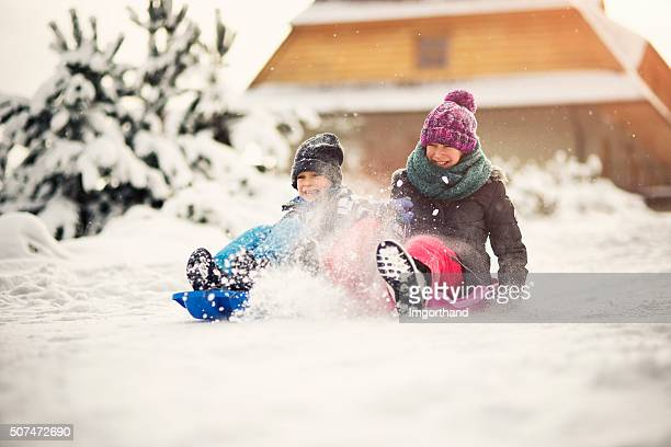 Brother and sister tobogganing in winter forest