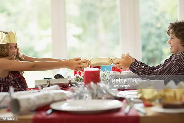 Bruder und Schwester tugging Christmas cracker
