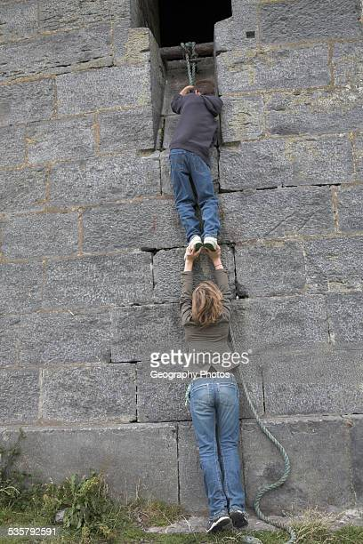 brother and sister twins pulling themselves up a rope against a stone wall