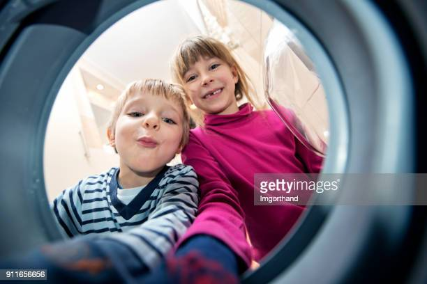 Brother and sister unloading a washing machine