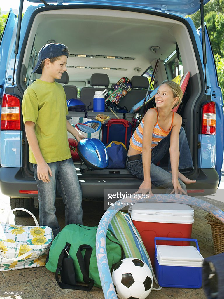 Brother and Sister Unloading Objects From an SUV Car : Stock Photo