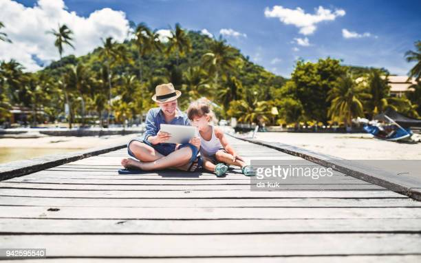 brother and sister using digital tablet at vacation - ko samui stock photos and pictures