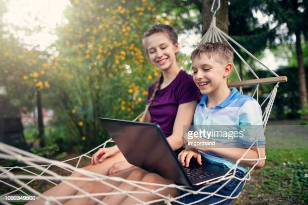 brother and sister using laptop on hammock - lazy poland stock photos and pictures
