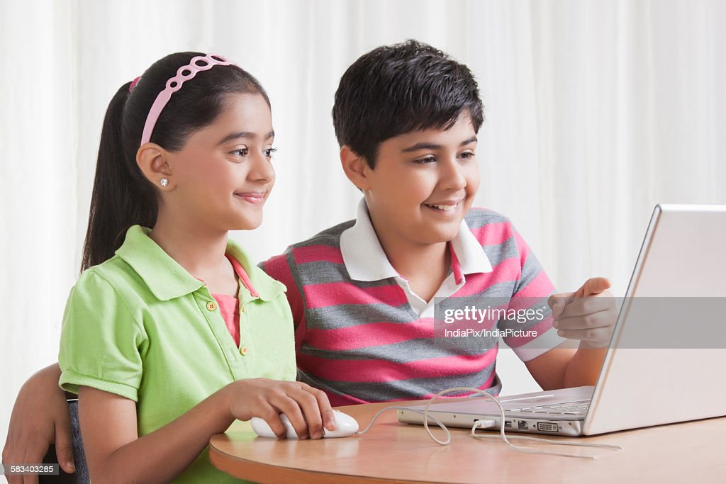 Brother and sister using laptop : Stock Photo