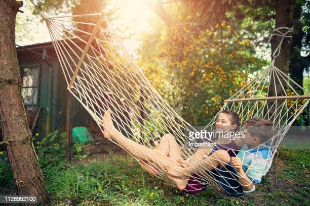 brother and sister using resting on hammock - lazy poland stock photos and pictures