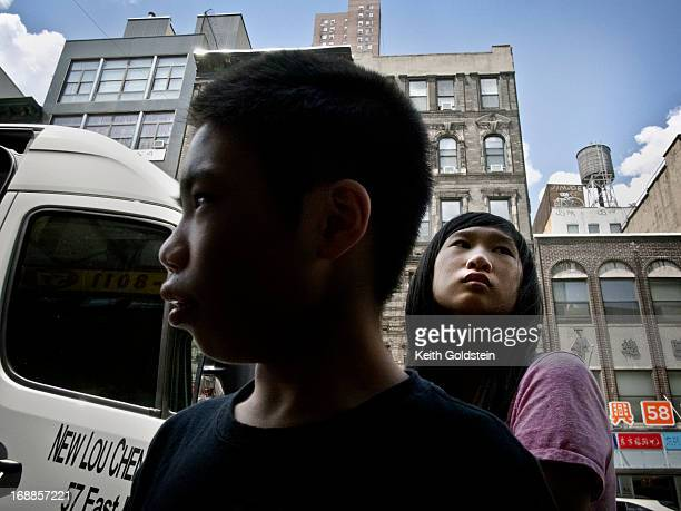 Brother and sister wait for their mother who is shopping on East Broadway, Chinatown, New York City.