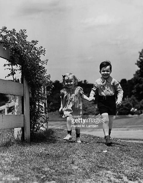 brother and sister walking holding hands - {{relatedsearchurl(carousel.phrase)}} ストックフォトと画像