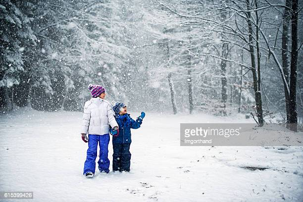 Brother and sister walking in snowy forest