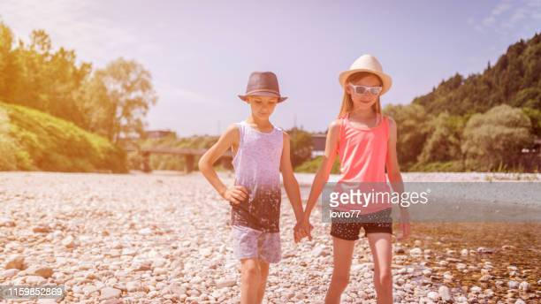 brother and sister walking near the river and holding hands - thin stock pictures, royalty-free photos & images