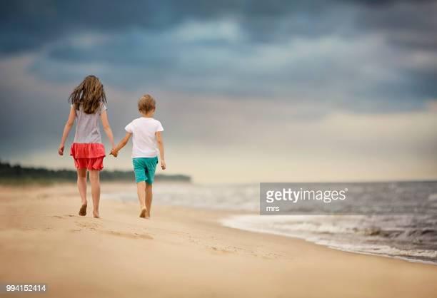brother and sister walking on beach - somente crianças imagens e fotografias de stock