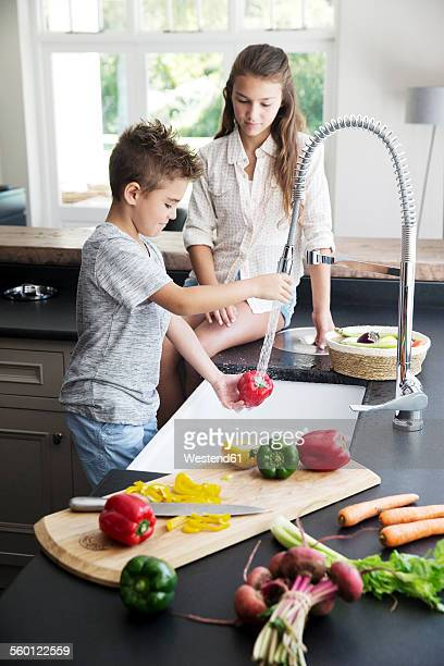 Brother and sister washing vegetables in kitchen