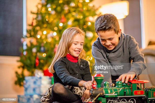 brother and sister watching a toy train - children pantyhose stock photos and pictures