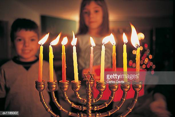 brother and sister watching candles burning on a menorah during hannukah - hanukkah imagens e fotografias de stock