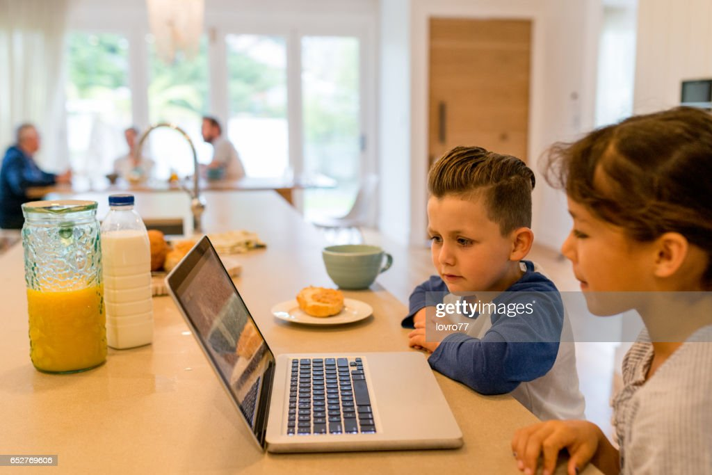Brother and sister watching cartoons on a laptop in the kitchen during breakfast : Foto stock