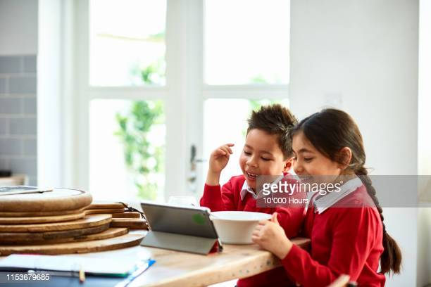 brother and sister watching tablet at breakfast and smiling - primary school child stock pictures, royalty-free photos & images