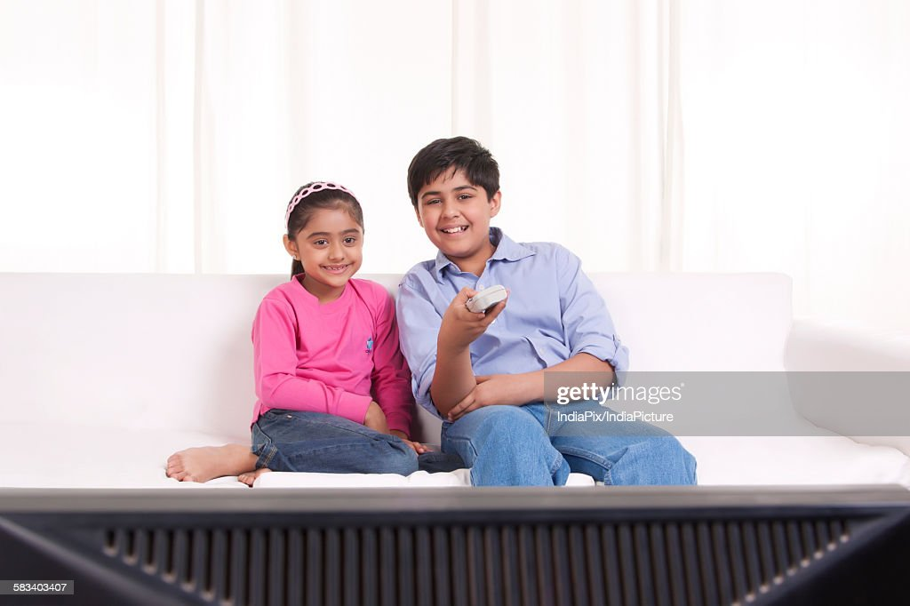 Brother and sister watching tv : Stock Photo