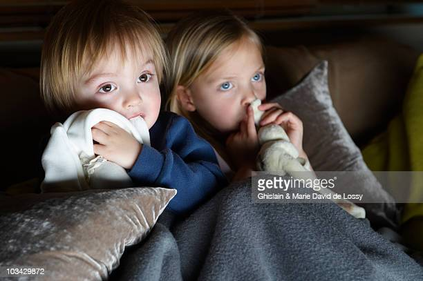 Brother and sister watching tv with their blankets