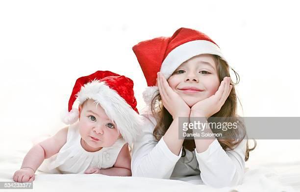 Brother and sister wearing santa hats