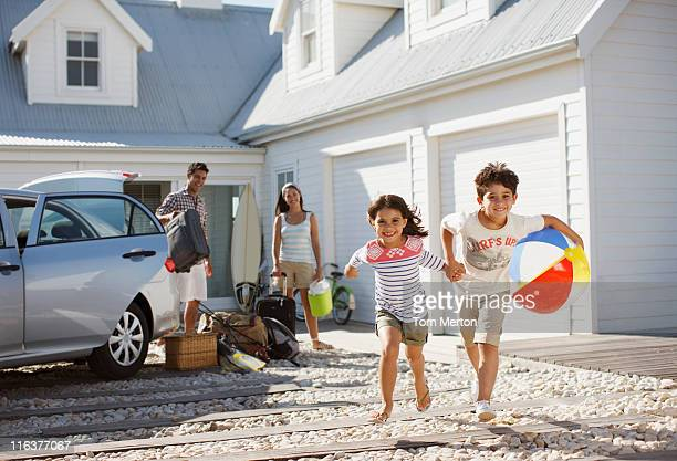 brother and sister with beach ball running on driveway - beach house stock pictures, royalty-free photos & images