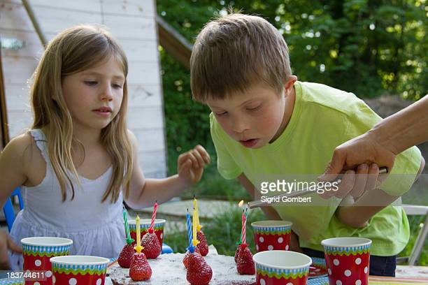 brother and sister with birthday cake - sigrid gombert stock-fotos und bilder