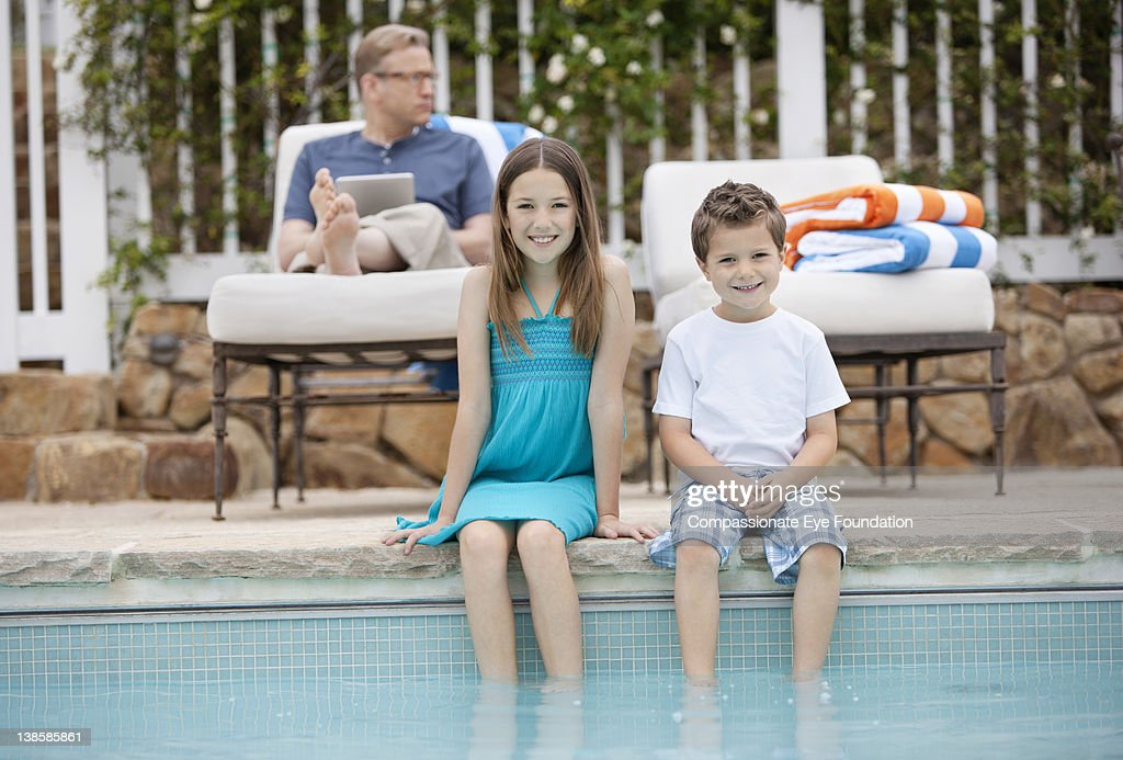 Brother and sister with feet in swimming pool : Stock Photo