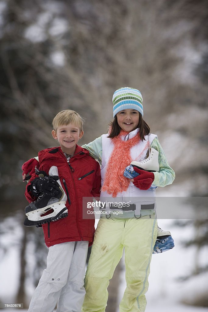 Brother and sister with ice skates : Stockfoto