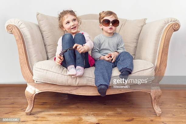 Brother and sister with oversized sunglasses sitting on couch