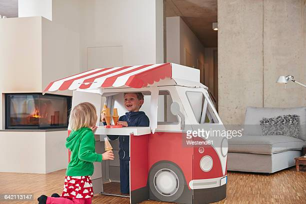 brother and sister with popsicles and model ice cream van in living room - lolly models stock pictures, royalty-free photos & images