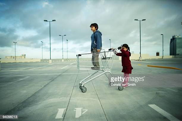 Brother and sister with shopping trolley