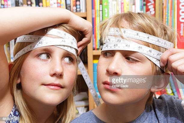 brother and sister with tape measures around heads - people with both male and female organs stock photos and pictures