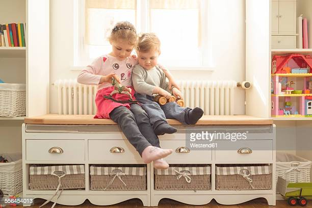 Brother and sister with wooden toys at home