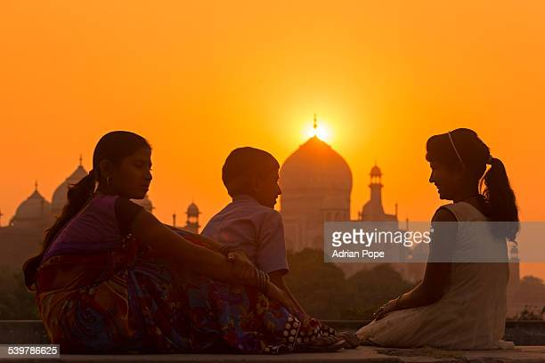 Brother and sisters chatting at sunset