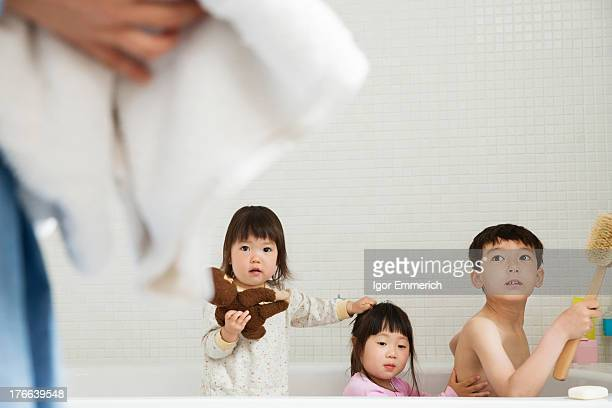 Brother and sisters in bath playing