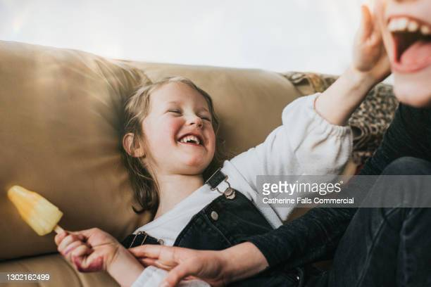 brother attempting to lick his younger sisters ice lolly as laughs and pushes him away - laughing stock pictures, royalty-free photos & images