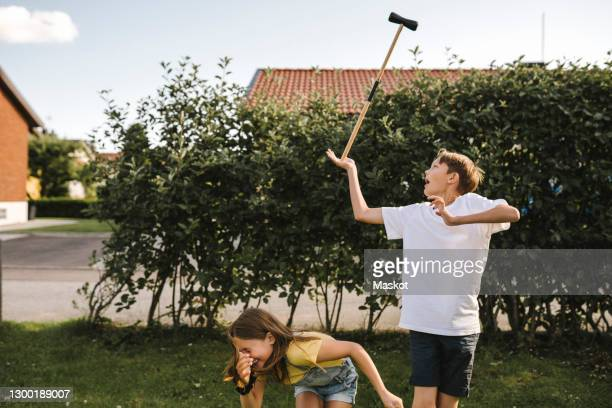 brother balancing polo mallet by sister in back yard - polo stock pictures, royalty-free photos & images