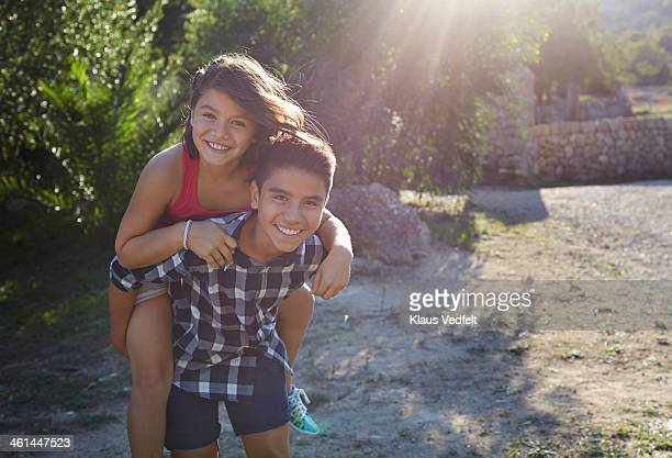 brother carrying sister on the back at sunset - klaus vedfelt mallorca stock pictures, royalty-free photos & images