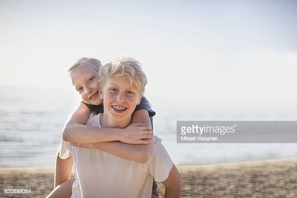Brother carrying sister piggyback on the beach