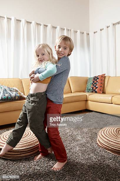 Brother carrying younger brother in living room.