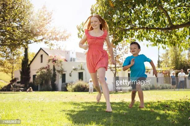 brother chasing sister in garden - bruder stock-fotos und bilder