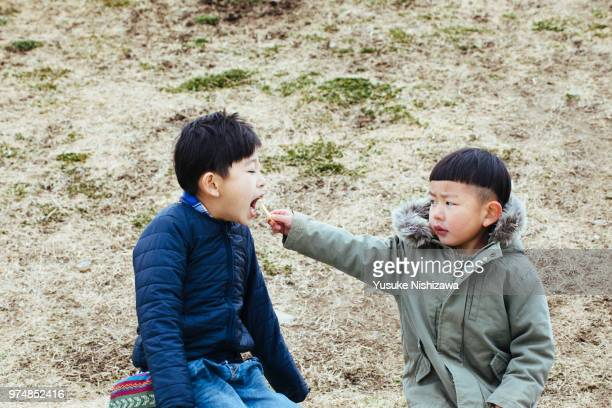 a brother gives a french fries to his brother - yusuke nishizawa fotografías e imágenes de stock