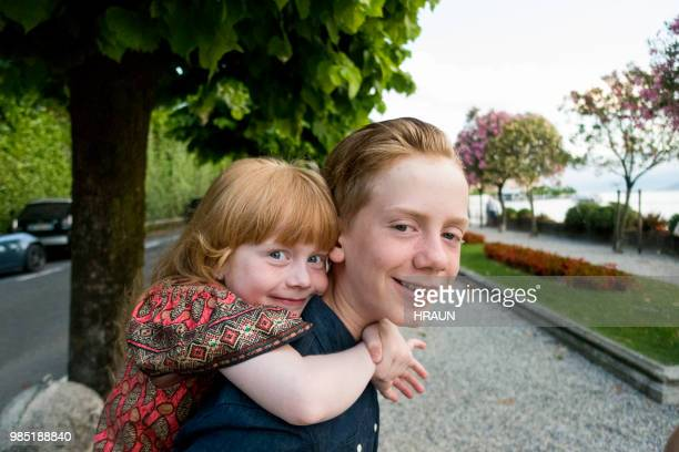 brother giving sister piggyback in belaggio como, italy. - growing pains stock pictures, royalty-free photos & images