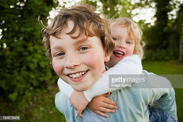 Brother giving sister piggyback