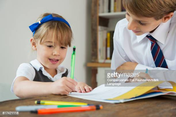 Brother helping sister with homework at kitchen table