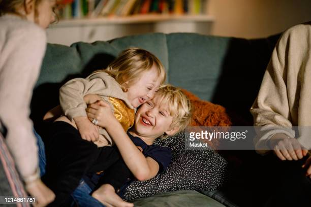 brother holding sister with down syndrome while playing on sofa at home - disabilitycollection stock-fotos und bilder