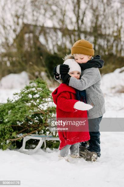 brother hugs sister during christmas - country christmas stock pictures, royalty-free photos & images