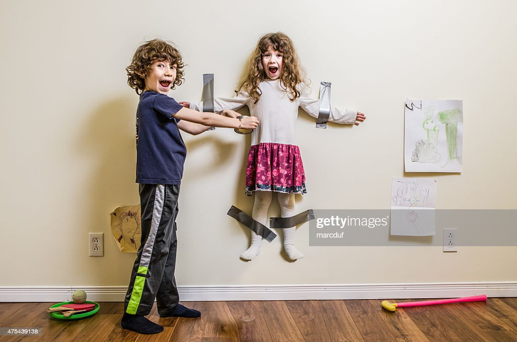 Brother hung her sister on the wall : Stock Photo